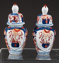 Pair of Japanese Imari vases each with bell shaped covers with onion finial conforming bodies having floral painted reserves, 6.50