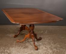 Two pedestal Queen Anne style mahogany dining table with burl walnut banded top and three leaves, bases have urn shaped columns and three cabriole legs with shell carved knees and pad feet, 48