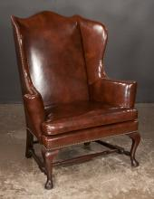 Queen Anne mahogany brown leather wing chair with shaped back, scroll arms and on cabriole legs with pad feet and stretcher, 38