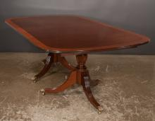 Two pedestal Sheraton style mahogany dining table with burl walnut banded top, pedestals have urn shaped columns with acanthus leaf carving and fluted legs, 48
