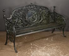 Wrought iron garden bench with circular panel in the back depicting a seated lady with bird perched on her finger, pierced back with leaf and bird design, cannonball finials on curved legs with hoof feet, 72