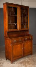 Sheraton style mahogany bookcase cabinet, top section has leaded glass doors, base has two drawers over two panelled doors and shaped apron, 47