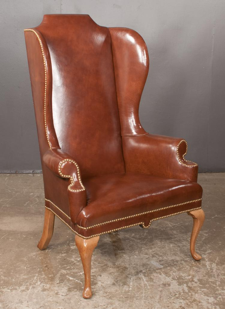 Queen Anne style high back wing chair covered in brown leather with brass nail trim, 32