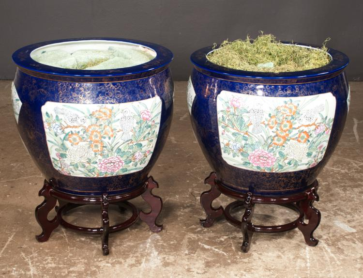 Pair of cobalt blue and gold Chinese porcelain fish bowls with multicolor bird and floral decoration on wooden stands, 19