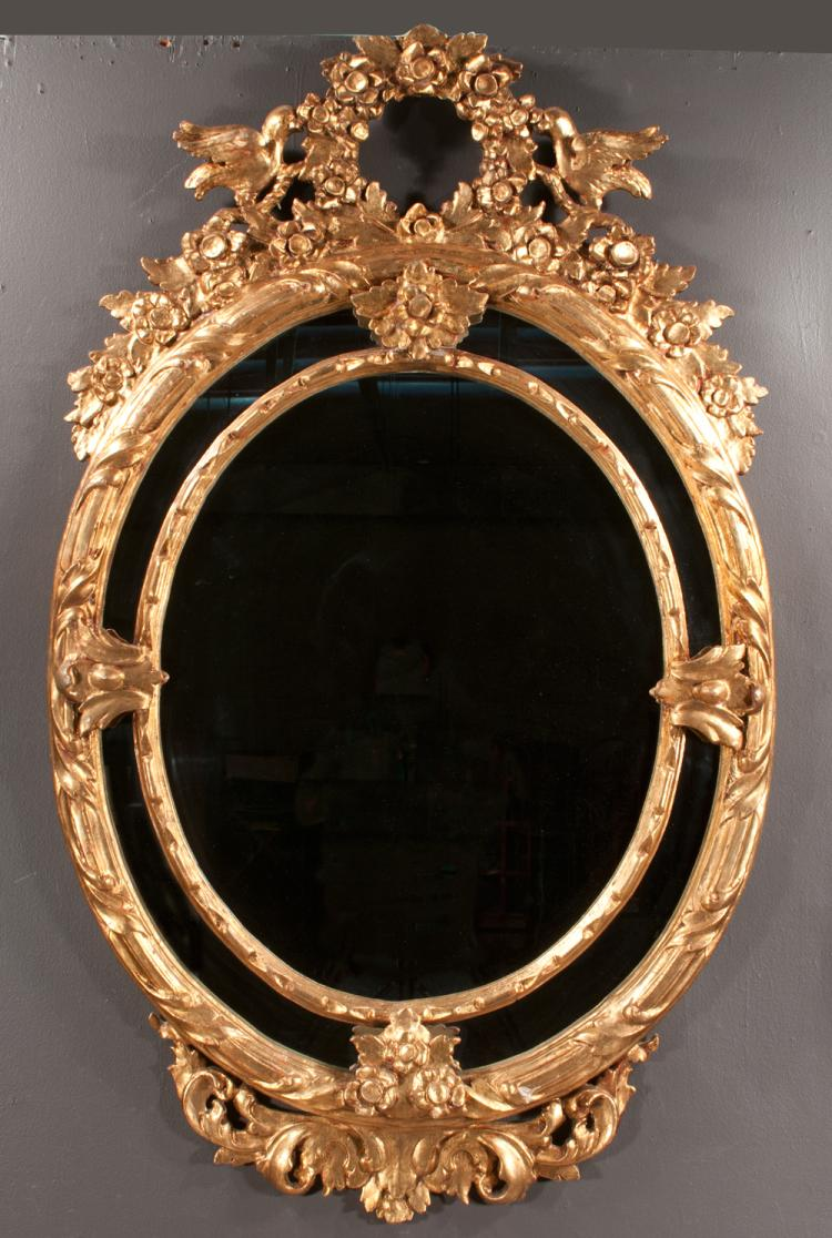 Venetian oval gold leaf mirror with floral wreath designed pediment with birds on each side and floral decoration at the base, 65