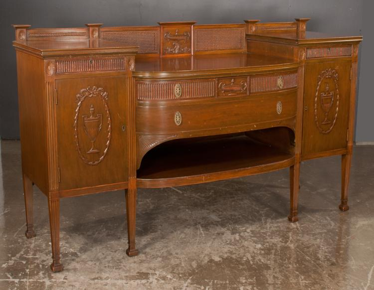 Sheraton style mahogany sideboard with bow front center section, carved urn on back gallery and on each end door on square tapered fluted legs with splay feet, c.1900, 72