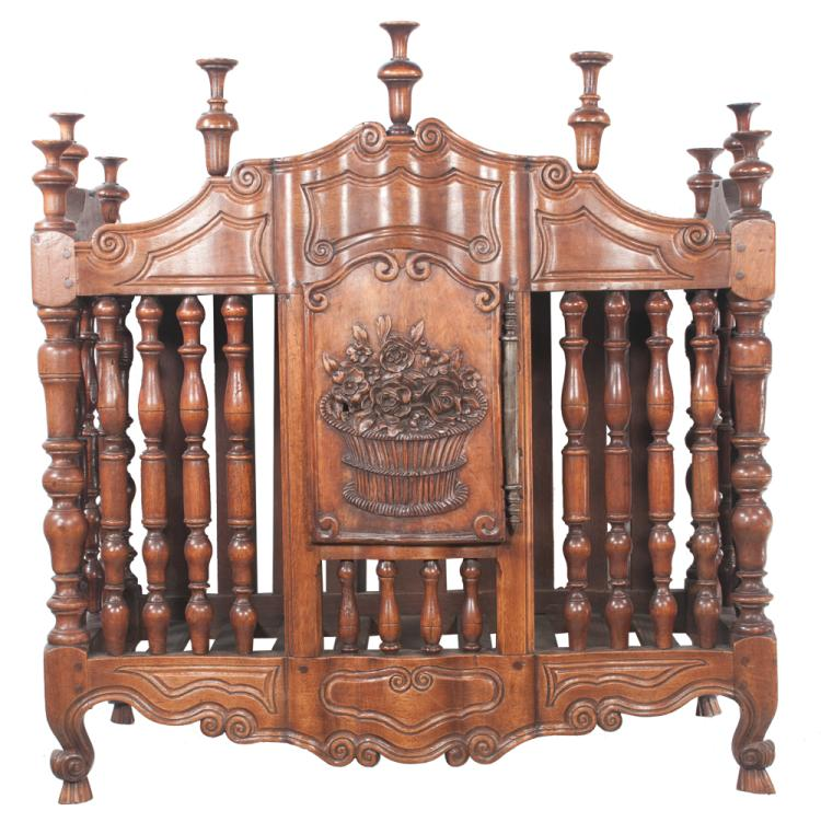Country French serpentine front walnut panettiere with arched pediment, turned finials, center door with carved basket of flowers, turned spindle sides and carved apron, c.1860, 33