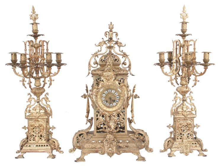 Louis XVI bronze clock set, clock has mask and pierced scroll filigree design and enamel numerals, 15