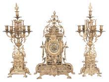 Louis XVI bronze clock set, clock has mask and pierced scroll filigree design and enamel numerals, 15
