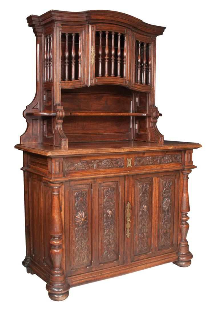 Two part country French oak cabinet with panettiere top section with turned finials, base has one long drawer with carved fronts, double carved doors in base and on bun feet, c.1860, 52