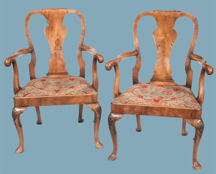 Pair of Queen Anne walnut armchairs with scroll carved urn shape backs, needlepoint cushions on cabriole legs with pad feet, c.1900, 24