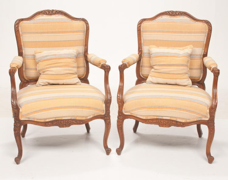 Pair of Louis XV style walnut fauteuils with arched and floral carved backs, shaped arms on carved cabriole legs with scroll carved feet, 27