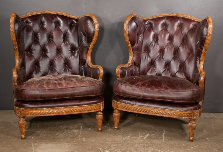 Pair of Louis XVI style wing chairs with carved aprons and on tapered fluted legs, covered in brown leather with tufted backs and loose cushions, 35