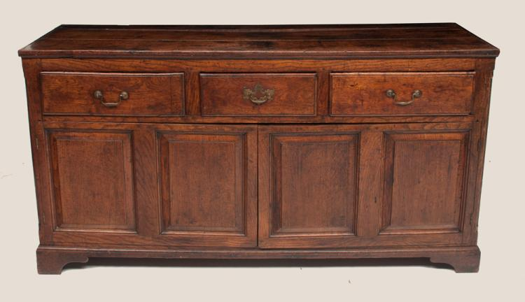 Lancashire County oak dresser base with three drawers below the top above double panel doors on bracket feet, c.1780, 60