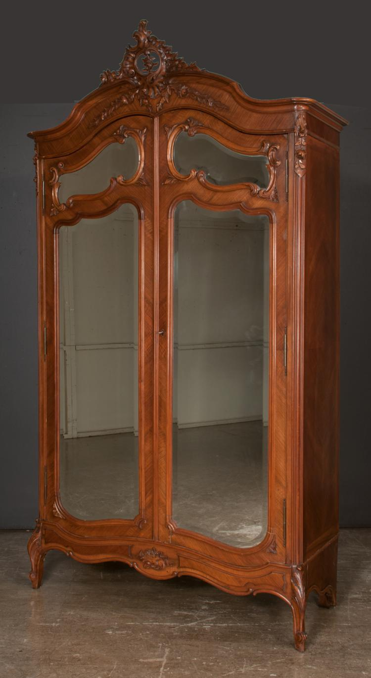 Louis XV carved walnut armoire with pierced scroll and floral pediment, bevelled mirror doors with carved apron and scroll carved feet, 52