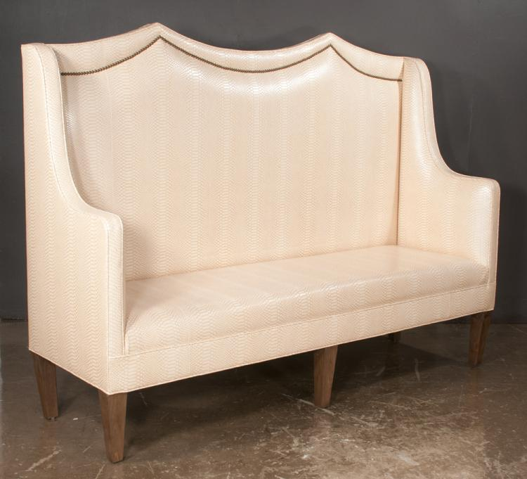 Custom made sofa with double arch panel back on straight tapered legs covered in a custom imitation leather fabric, with brass nail head border at the top, 79