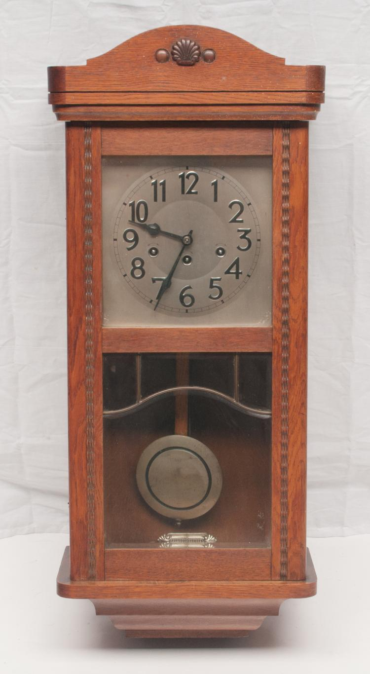 German oak chiming wall clock with arched pediment and bevel leaded glass door, 13