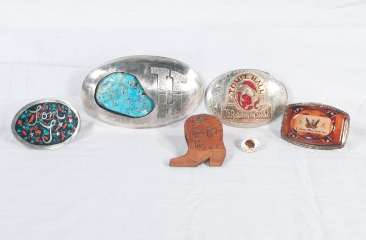 Group of four belt buckles, one silver buckle with T.T.H. and a large turquoise stone, one silver buckle with Tom T. Hall Crazy Horse, one silver buckle with enamel center with Tom T. and one Calhoun Musicland buckle, along with a Tom T. leather boot shape key chain