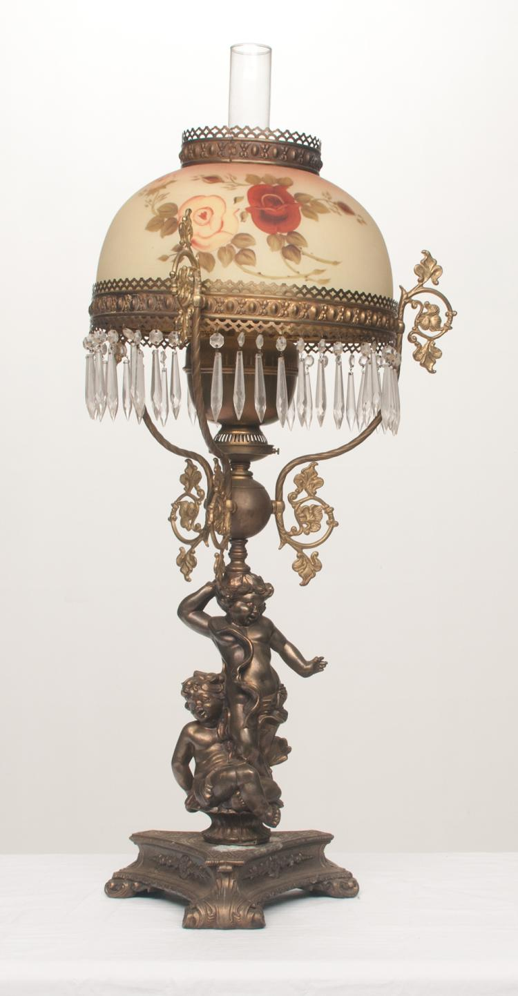 Brass oil lamp with figures of two putti in the column and on a triangular shaped base with a hand painted glass shade, 12