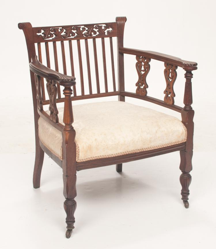 American Victorian armchair, back has pierced scroll carved rail at top above 10 spindles, two pierced carved splats on each side of arms on tapered fluted legs, c.1920, 26