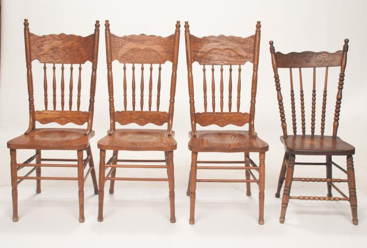 Group of three American oak kitchen chairs with scroll carved panel above a spindle back, shaped seats and turned legs with stretcher, 17.5