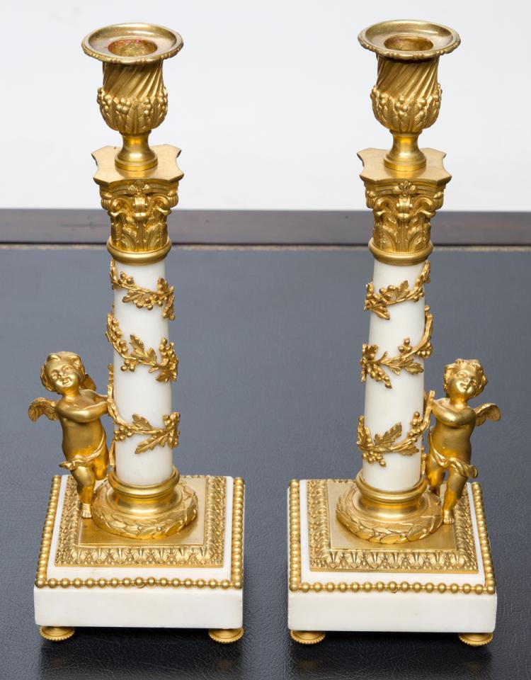 Pair of Louis XVI white marble candlesticks with bronze ormolu mounts and a bronze ormolu cherub on the base of each candlestick, c.1890, 12.5