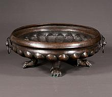 Circular bronze fluted centerpiece bowl with lion and ring mounts on four claw feet, 17
