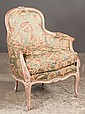 Louis XV style fruitwood bergere with floral carved back and apron, and covered in a green floral fabric, 27