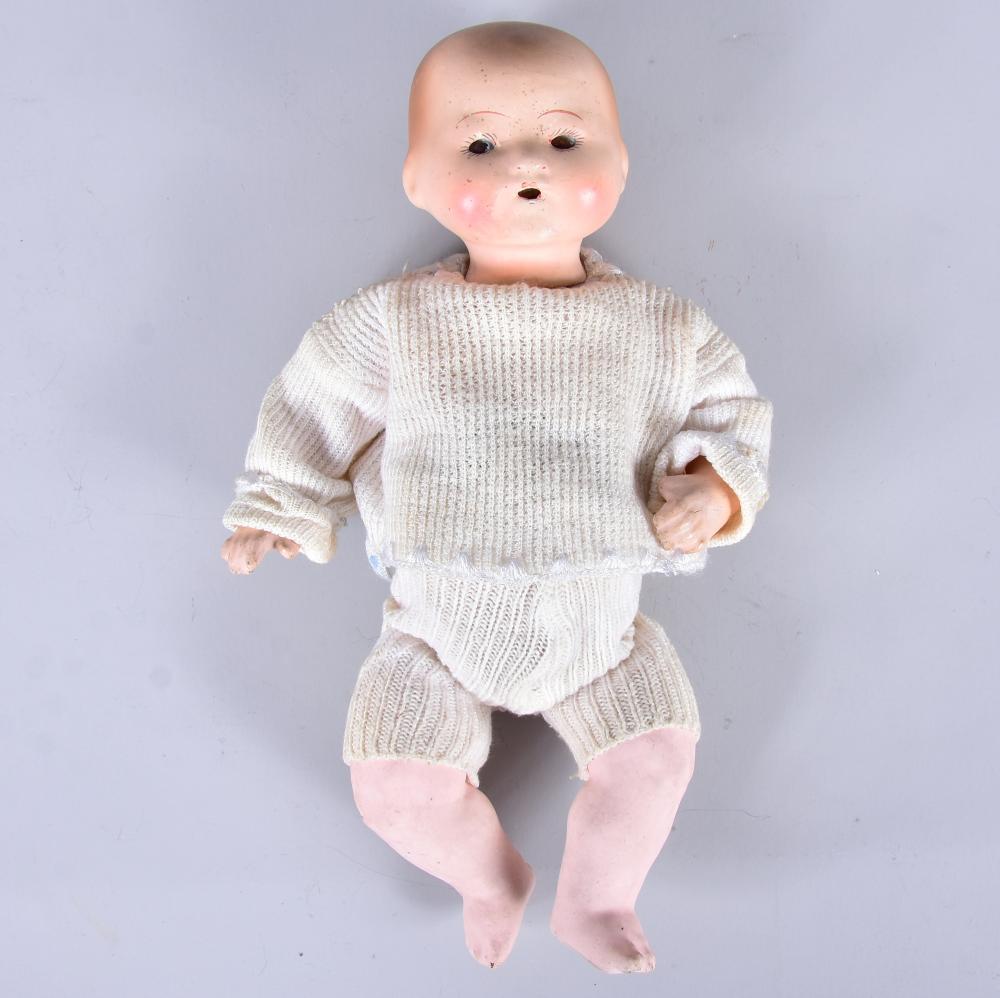 Babypuppe um 1910, Einbindekopf auf Massekörper gesetzt, Bauch des Körpers mit orig. Aussparung, ev. für Stimme, feststehende braune Glasaugen, Körper gut erhalten, L 26 cm