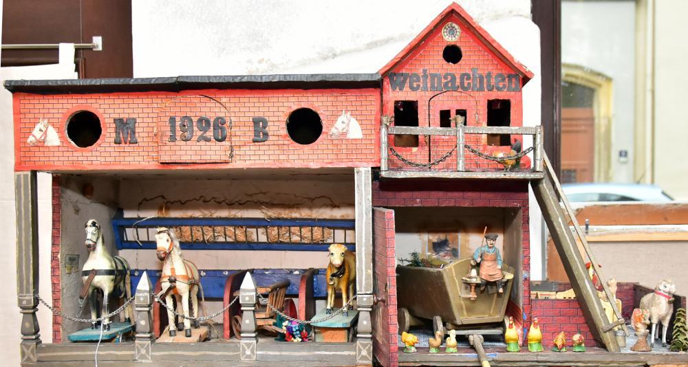 Pferdestall 1926, dazu versch. Massefiguren, Federvieh, Leiterwagen m. Kutscher (Masse, Beine def.), 2 Pferde, 1 Kuh, Sommergartenmöbel mit Puppe, Eigenbau aus wohlhabendem Haushalt, gut erhalten, Maß: 95x50x42cm
