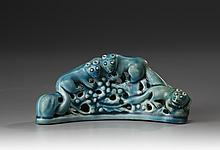 A turquoise-glazed brush rest