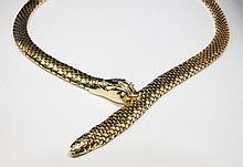 COLLIER en or jaune, stylisant un serpent en enroulement, maille souple, la tête est également stylisée et les yeux sont ornés de rubis. Poids brut : 44,1 g Longeur porté : 21,5 cm  A yellow gold and ruby necklace.