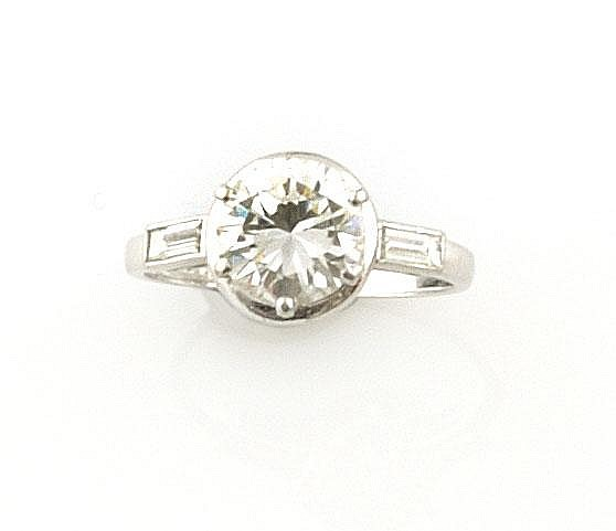 BAGUE SOLITAIRE en platine ornée d'un diamant de taille moderne de 1,95 carat, épaulé de deux diamants de taille baguette. Poids brut : 3,3 g TDD : 51 A 1,95 CTS ROUND SHAPED DIAMOND SOLITAIRE AND PLATINIUM RING