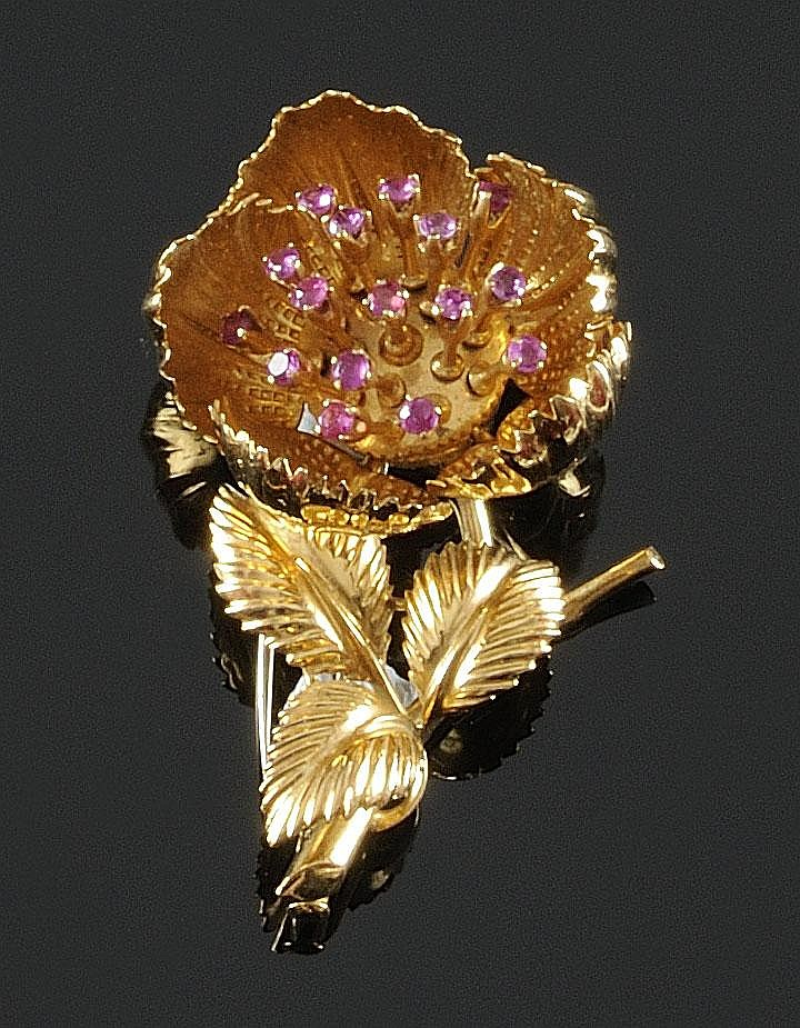 BROCHE en or jaune stylisant une fleur aux pétales articulés laissant apparaitrent un pistil de rubis de taille brillant. Poids brut : 24,4 g Hauteur : 5,5 cm A RUBY AND YELLOW GOLD BROOCH