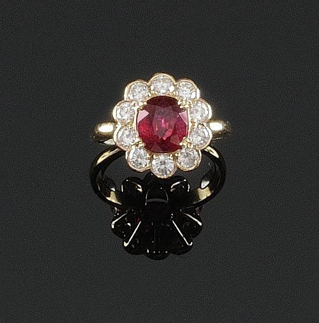 BAGUE en or jaune ornée en son centre d'un rubis de taille ovale de 2,34 carats dans un entourage de diamants de taille brillant. Poids brut : 5,4 g TDD : 56 -57 A RUBY, DIAMOND AND YELLOW GOLD RING