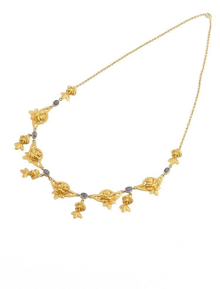 COLLIER en or jaune à décors de fleurs et feuillages, la monture ponctuée de saphirs de taille ovale sertis clos. Poids brut : 20,3 g A SAPPHIRE AND YELLOW GOLD NECKLACE