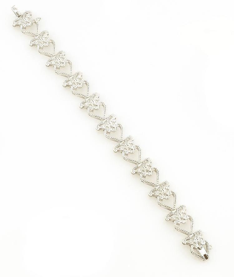 BRACELET en or gris, le motifs ajouré et ciselé, retenant onze diamants sertis clos, la monture ponctuée de diamants de taille brillant. Poids brut : 20,7 g A DIAMOND AND WHITE GOLD BRACELET