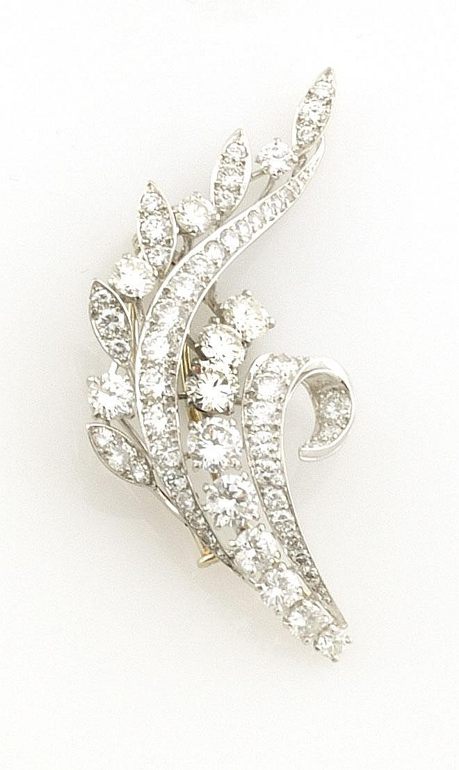 BROCHE en or gris stylisant des volutes serties de diamants de taille brillant. Poids brut : 11,3 g A DIAMOND AND YELLOW GOLD BROOCH
