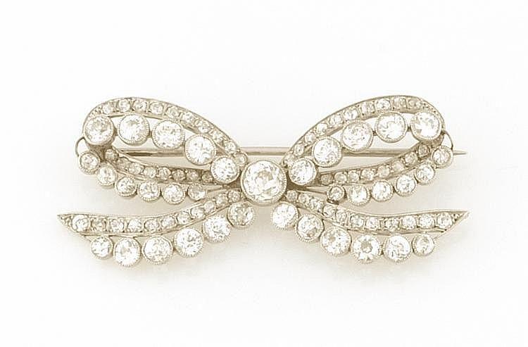 BROCHE en or gris stylisant un noeud plat retenant en son centre un diamant de taille ancienne, la monture ornée de diamants de taille ancienne. Poids brut : 12,3 g A DIAMOND AND YELLOW GOLD BROOCH