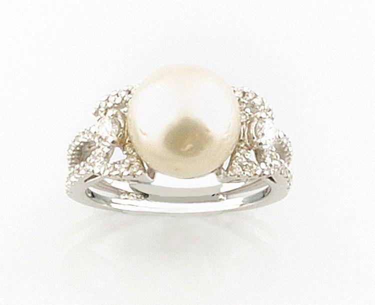 BAGUE en or gris retenant en son centre une perle de culture épaulée de deux diamants de taille brillant, la monture finement ajourée, pavée de diamants brillantés. Poids brut : 7,6 g TDD : 54 - 55 A PEARL, DIAMOND AND WHITE GOLD RING