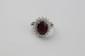BAGUE en or gris ornée d'un rubis de taille ovale probablement Birman de 3,5 carats dans un double entourage de de diamants brillantés. Poids brut : 6,1 g TDD : 54  A ruby, diamond and white gold ring.