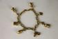 BRACELET en or jaune composé d'une chaine figaro partiellement tosadée retenant en pampille sept breloques stylisant une cage, un dé, un sabot, un carrosse, un lapin, un caeur et un couple.  Poids brut: 25,5 g.  Longueur: 8,5 cm.