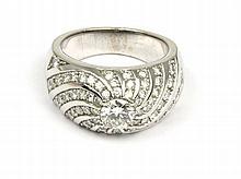 BAGUE en or gris bombée la monture ornée d'un pavage de diamants, retenant en son centre un diamant de taille brillant. Poids brut : 12,8 g  TDD : 53