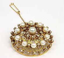 BROCHE en or jaune de forme ronde ornée d'une succession de onze perle et de diamants de taille brillant.  Poids brut : 36,1 g Diam : 5 cm