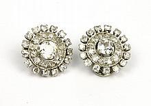 PAIRE DE BOUCLES d'oreilles en or gris ornée en son centre de deux diamants de taille brillant dans un double entourage de diamants de taille brillant et de pierres blanches Poids brut : 10,2 g