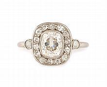 BAGUE en or gris et platine, ornée en son centre d'un diamant coussin taille ancienneen serti clos, dans un entourage de diamants taille ancienne, la monture réhaussé de deux diamants de taille ancienne. Poids brut : 4 gr TDD : 50 A platinum, white