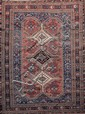 Ancien AFCHAR (Perse) à décor géométrique de pierres de couleur, diamants et crabes sur fond vieux rose, orné de trois médaillons à fers de lances. Vers 1930 123 x 135