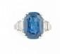 BAGUE en or gris et platine ornée d'un saphir de taille ovale d'environ 6 carats épaulé de deux diamants de taille baguette en chute.  Poids brut : 8,1 g TDD : 46  A sapphire, diamond and platinium