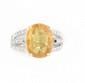 BAGUE en or gris ornée d'un saphir jaune de taille ovale de 4,4 carats, la monture ajourée et pavée de diamants de taille brillant. Poids brut : 5,5 g TDD : 50  A yellow sapphire, diamond and white gold ring