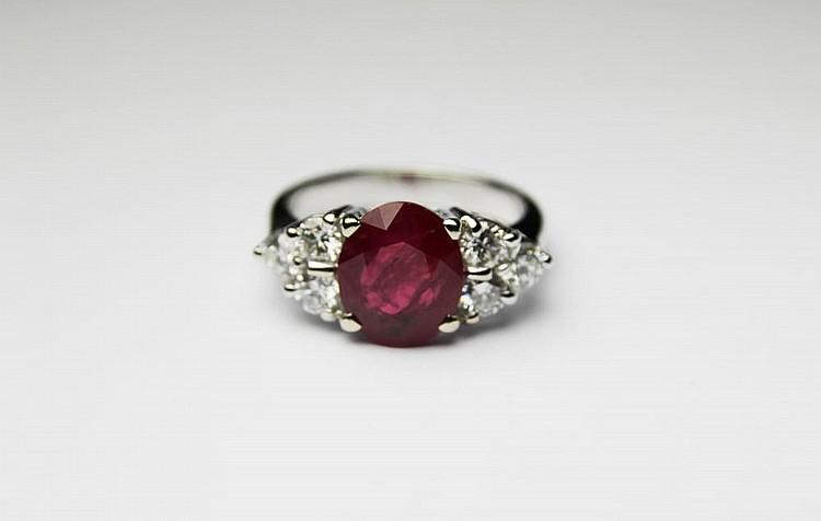 BAGUE en or gris ornée d'un rubis de taille ovale de 3,12 carats épaulé de six diamants de taille brillant. Poids brut : 6,2 g TDD : 52 A RUBY, DIAMOND AND WHITE GOLD RING